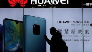 一名女性经过华为店铺前 正在浏览她的手机