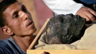 Un empleado del Servicio de Antigüedades de Egipto saca la momia de Tutankamón, el faraón niño, de su ataúd (foto de archivo).