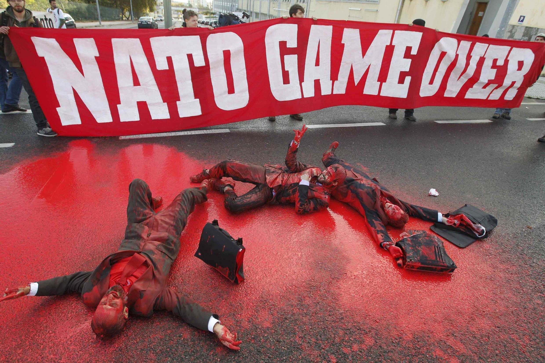 """Pacifistas pintados protestam neste sábado em Lisboa, diante do cartaz """"OTAN, o jogo acabou."""""""