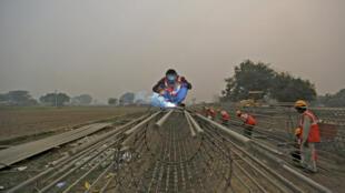 Des ouvriers travaillent à la construction d'un pont pour le métro de New Delhi, le 30 novembre 2015.