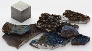 Fragments de manganèse pur à côté d'un cube de manganèse