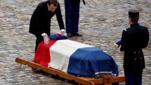 Le président Emmanuel Macron touche le cercueil drapé de l'ancien officier de la gendarmerie, le colonel Arnaud Beltrame, qui a été tué par un militant islamiste après avoir pris la place d'une femme en otage lors d'un siège de supermarché à Trebes.