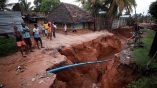 Moradores olham para uma estrada que desabou no rescaldo do ciclone Kenneth, na aldeia de Wimbe em Pemba, Moçambique.