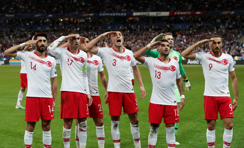 Jogadores turcos batem continência em apoio à ofensiva turca na Síria, contra os curdos, durante jogo no Stade de France, em 14 de outubro de 2019.