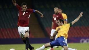 O jogador egípcio Eslam Ramadan na disputa pela bola com o brasileiro Rafael Silva durante a estreia da seleção brasileira nas Olimpíadas de Londres, nesta quinta-feira, dia 26 de julho.