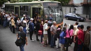 Le 14 mars 2019, des habitants de Caracas font la queue pour monter dans des bus mobilisés pour parer à la réouverture partielle du métro après la coupure d'électricité géante.