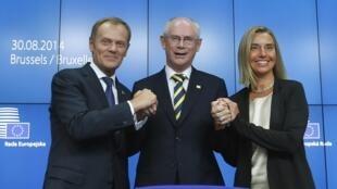 Le Premier ministre polonais Donald Tusk (g) et la ministre italienne des Affaires étrangères, Federica Mogherini (d) sont félicités par le président sortant du Conseil, Herman  Van Rompuy (c). Bruxelles, le 30 août 2014.