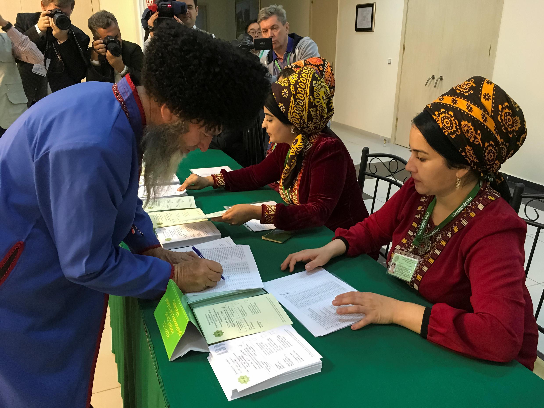 Un homme récupère son bulletin de vote à Ashgabat, lors des élections législatives turkmènes, le 25 mars 2018.