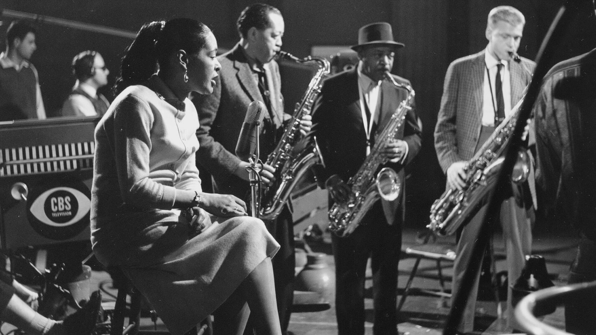 La chanteuse Billie Holiday accompagnée des musiciens : Lester Young (à gauche), Coleman Hawkins et Gerry Mulligan, pendant l'émission de télévision sur CBS «The sound of jazz», le 8 décembre 1957 à New York.