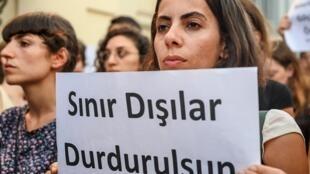 Une activiste des droits de l'homme en Turquie tient une pancarte sur laquelle on peut lire : Stop aux déportations. Cette photo a été prise à Istanbul le 2 août 2019 lors d'une manifestation contre les expulsions des réfugiés.