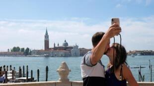 Des touristes prennent un selfie à Venise, le 14 juin 2020.