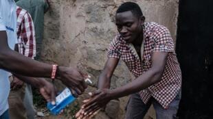 Un agent de santé fournit du gel hydroalcoolique à un homme dans la maison du premier Kényan diagnostiqué positif au Covid-19. Le 12 mars 2020 à Nairobi.