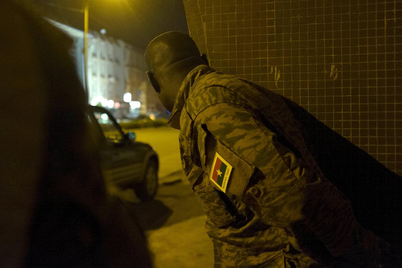 Caché derrière un mur, un soldat burkinabè inspecte les environs de l'hôtel attaqué par un commando jihadiste le vendredi 15 janvier à Ouagadougou.