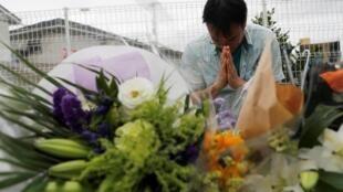 Мужчина молится возле стихийного мемориала у стен сгоревшей студии