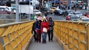 Migrantes que deixaram a Venezuela atravessam ponte Rumichaca International, entre a Colômbia e o Equador.