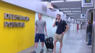 US Olympic swimmers Gunnar Bentz and Jack Conger walk to the airport police station office at Rio's international airport in this still frame taken from video on 17 August 2016.