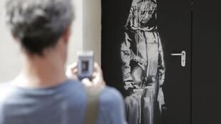 Man takes a photograph of graffiti artist Banksy's tribute to Paris terror victims.