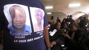 Un homme avec un t-shirt avec les portraits de Floribert Chebeya et Fidèle Bazana attend, en avril 2013, le procès d'un des principaux accusés dans l'affaire.