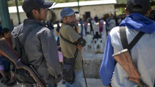 Un grupo de personas hace cola para votar en la comunidad nahua de Ayahualtempa, en el estado mexicano de Guerrero, el 6 de junio de 2021, ante la vigilancia de un grupo de autodefensa civil