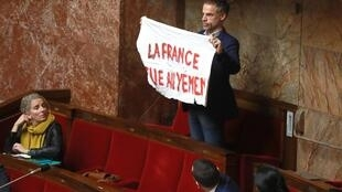 French lawmaker Sebastien Nadot in parliament holds up a banner that reads, 'France kills in Yemen', 19 February 2019.