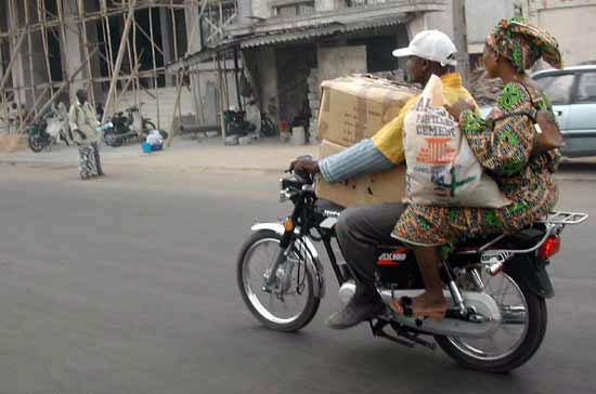 Un zémidjan (moto-taxi) transporte une cliente et ses bagages.
