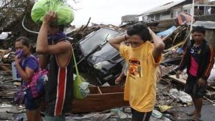 Жители Таклобана закрывают нос, защищаясь от запаха, исходящего от руин. Филиппины 12/11/2013