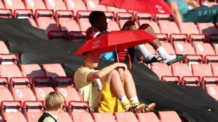 Arsenal midfielder Mesut Ozil (C) shelters from the sunshine beneath an umbrella