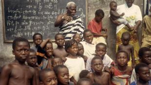 Frédéric Brumy Bouabré enseignant l'alphabet bété chez lui à Marcory‐Anoumabo, un quartier d'Abidjan, en 1995.
