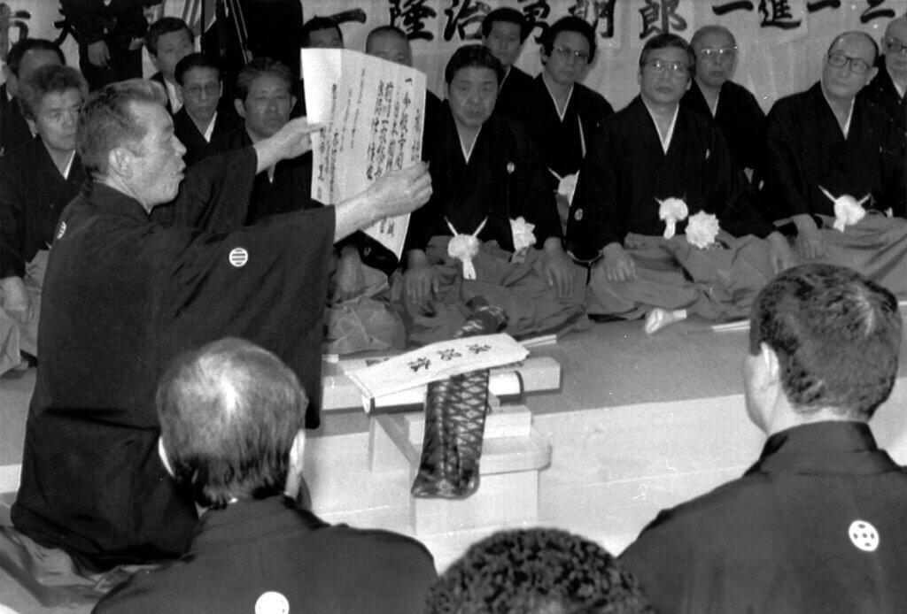 """The new boss, left of a Tokyo area yakuza syndicate, reads aloud his pledge of allegiance to the """"family,"""" country and Amaterasu, the sun goddess, during a recent succession ceremony witnessed by some 70 underwold bosses during February/March 1991."""