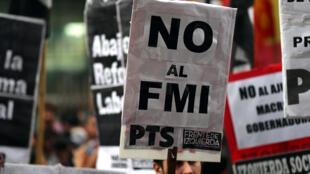 """Un homme brandit une pancarte """"Non au FMI"""" lors d'une manifestation à Buenos Aires en Argentine le 9 mai 2018."""