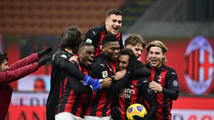 Le milieu de terrain turc de l'AC Milan, Hakan Calhanoglu (3e d), félicité par ses coéquipiers après avoir marqué le pénalty victorieux (0-0, 5-4 t.a.b) face au Torino, en 8e de finale de la Coupe d'Italie, le 12 janvier 2021 à Milan