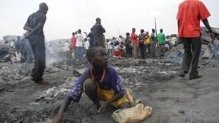 A young boy sifts through the remains of a stall at the Owino market in Kampala, Uganda