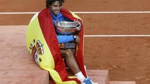 Rafael Nadal of Spain poses with the trophy and the Spanish flag
