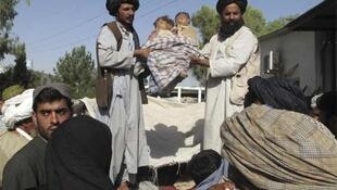 Villagers hold the bodies of two children killed in the Helmand province air strike