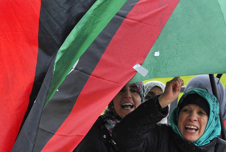 Manifestantes antigubernamentales protestan mientras los vientos de guerra hacen flamear las banderas.