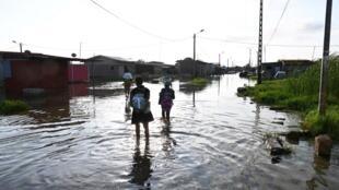 Des habitants de Grand Bassam marche dans une rue inondée après de fortes pluies, en Côte d'Ivoire, le 11 octobre 2019.