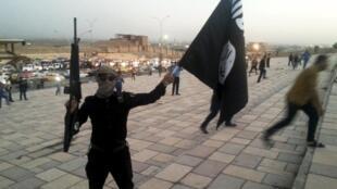 Mayakin kungiyar IS rike da tuta a birnin Mosul a 2014.