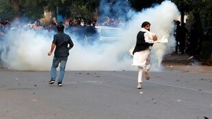 Manifestantes correm para escapar do gás lacrimogêneo disparado durante o protesto contra a nova lei de cidadania em Nova Délhi em 15 de dezembro de 2019.