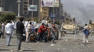 Security forces forcefully remove Muslim Brotherhood supporters in Cairo.
