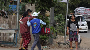 Una manifestante herida es atendida por personal médico tras ser golpeada po las fuerzas de seguridad durante una manifestación contra el golpe militar en Birmania, el 20 de febrero de 2021 en la ciudad de Mandalay