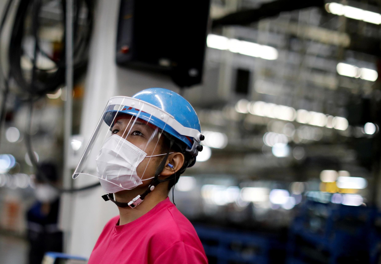 Employé de l'usine Mitsubishi de Kawasaki, au Japon, portant une visière et un masque de protection (photo d'illustration).