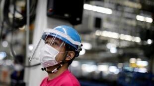 Employé de l'usine Mitsubishi de Kawasaki, au Japon, portant une visière et un masque de protection face au coronavirus.