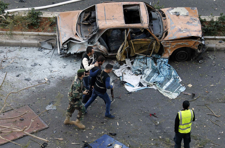 des policiers libanais encadrent un suspect, à proximité de l'attentat à la voiture piégée qui a fait au moins cinq morts, ce vendredi 27 décembre.