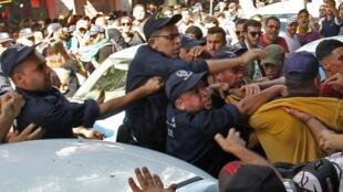 Des officiers de police algériens affrontent des manifestants lors d'une manifestation antigouvernementale dans la capitale, Alger, le 8 octobre 2019.