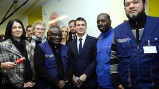 Le Premier ministre Manuel Valls (C) entouré du personnel du Centre du Samu social de Montrouge, dans la banlieue parisienne, le 31 décembre 2014.