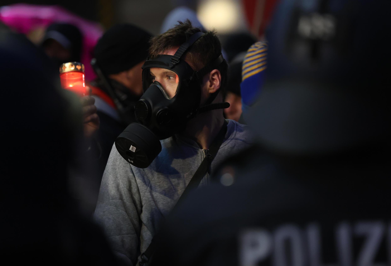 """Un manifestante del movimiento """"Querdenken"""" lleva una máscara de gas mientras participa en una protesta contra las medidas impuestas por el gobierno alemán para limitar la propagación del nuevo coronavirus, el 21 de noviembre de 2020 en Leipzig."""