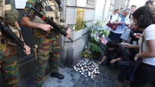 Des citoyens déposent des bougies devant l'entrée du Musée juif de Bruxelles, un an après l'attentat qui a causé la mort de quatre personnes.