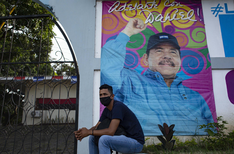 Un hombre se sienta frente a una pancarta que promueve la reelección del presidente de Nicaragua, Daniel Ortega, en Managua el 24 de septiembre de 2021.