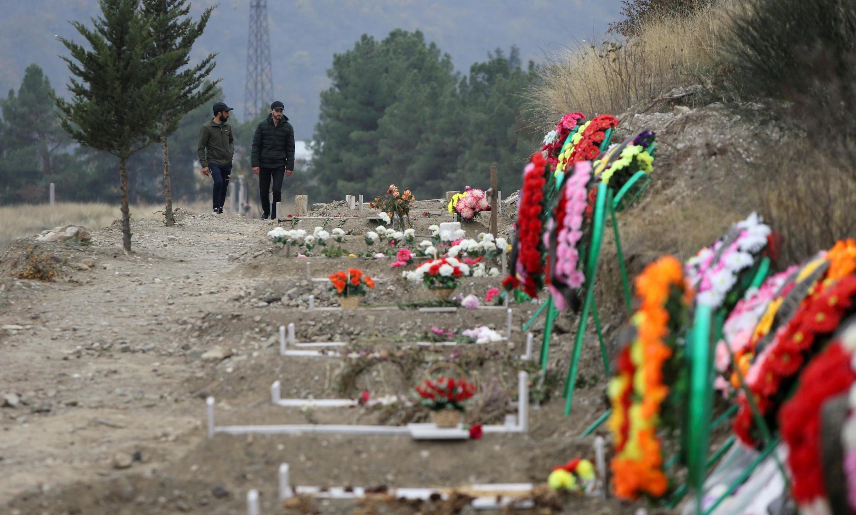 Des hommes longent des tombes de militaires et de civils tués dans les combats dans le Haut-Karabakh,