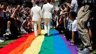 Gay newlyweds walk on a giant rainbow flag at a pro same-sex marriage party after registering their marriage in Taipei, Taiwan on 24 May, 2019.